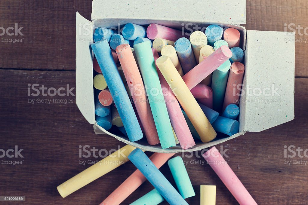 chalk in the box on wooden background stock photo