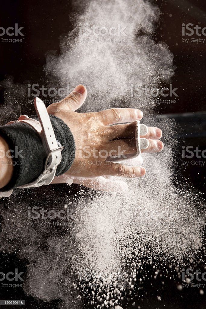 Chalk Powder Flies As Gymnast Preps for Bars stock photo