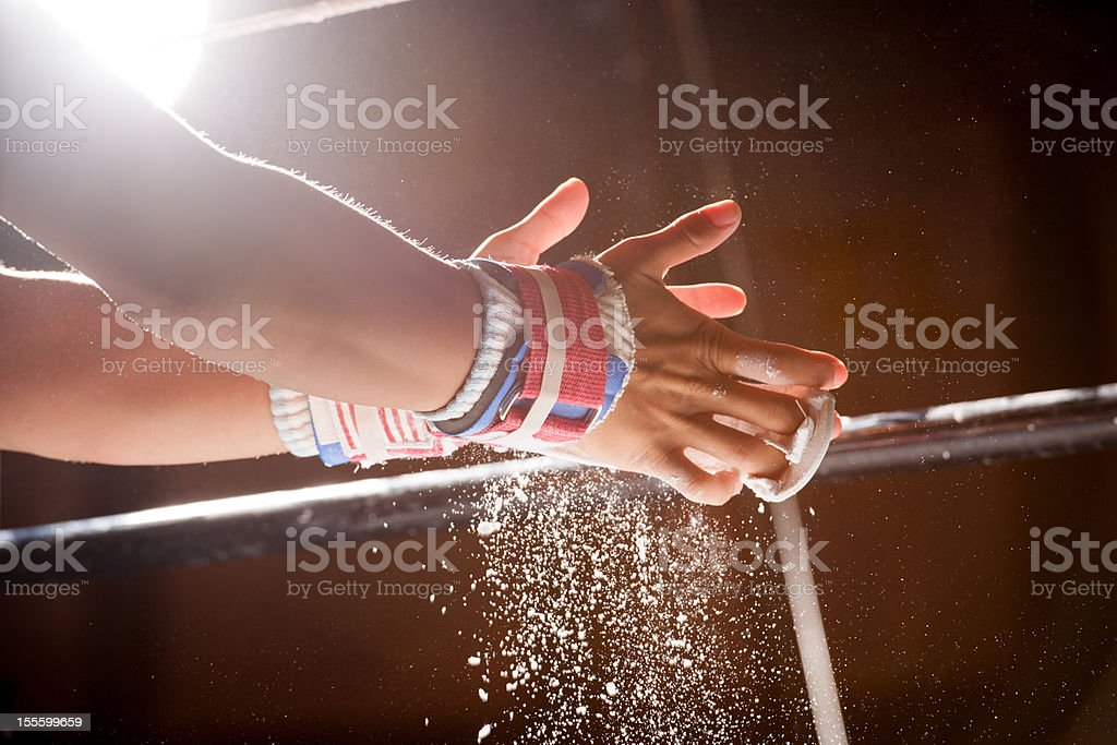 Chalk Power Falls from Hands as Gymnast Preps for Bars stock photo