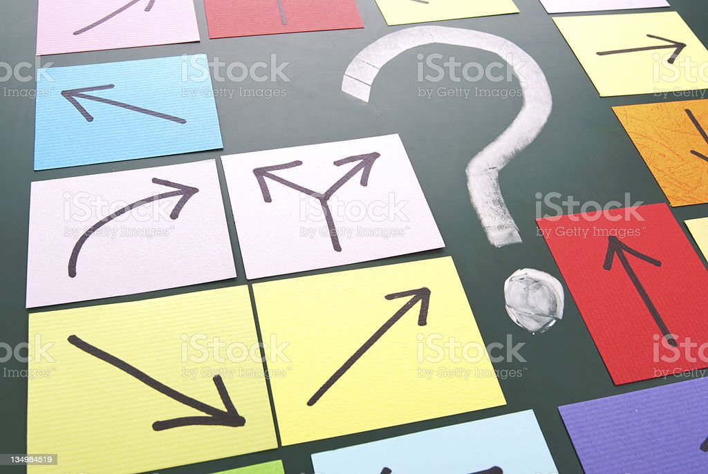 Chalk question mark surrounded by sticky note arrows stock photo