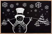 Chalkboard drawing of cute Christmas snowman in the wooden.