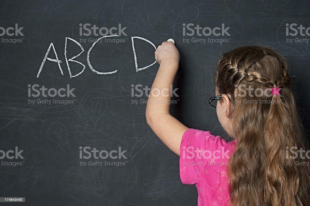 Chalkboard girl writing abcs royalty-free stock photo