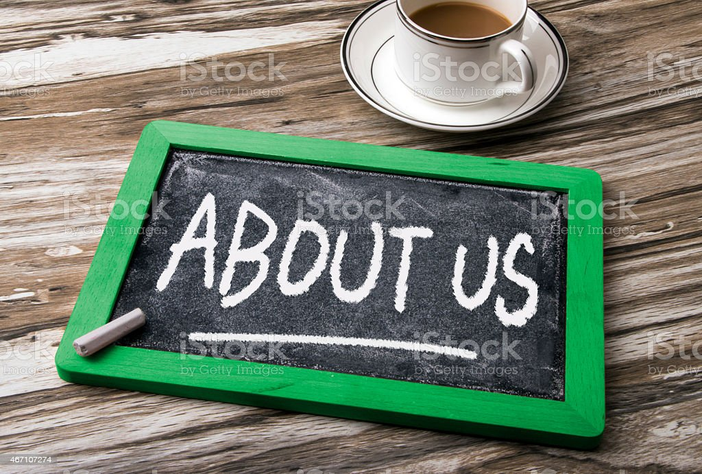 A chalkboard on a wooden table saying about us stock photo