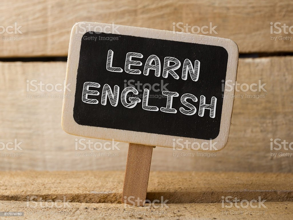 Chalkboard on wooden background with Learning English words stock photo