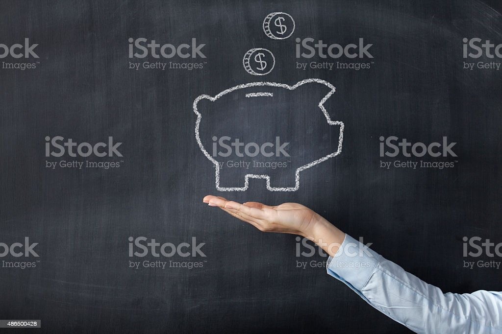 Chalkboard with hand and piggy bank stock photo