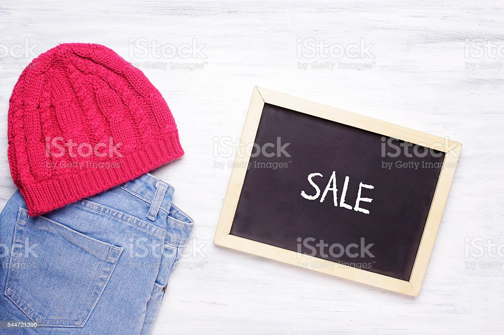 Chalkboard with SALE word and young woman's outfit white wooden stock photo