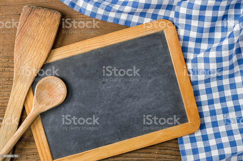 Chalkboard with wooden spoons on a blue checkered tablecloth stock photo