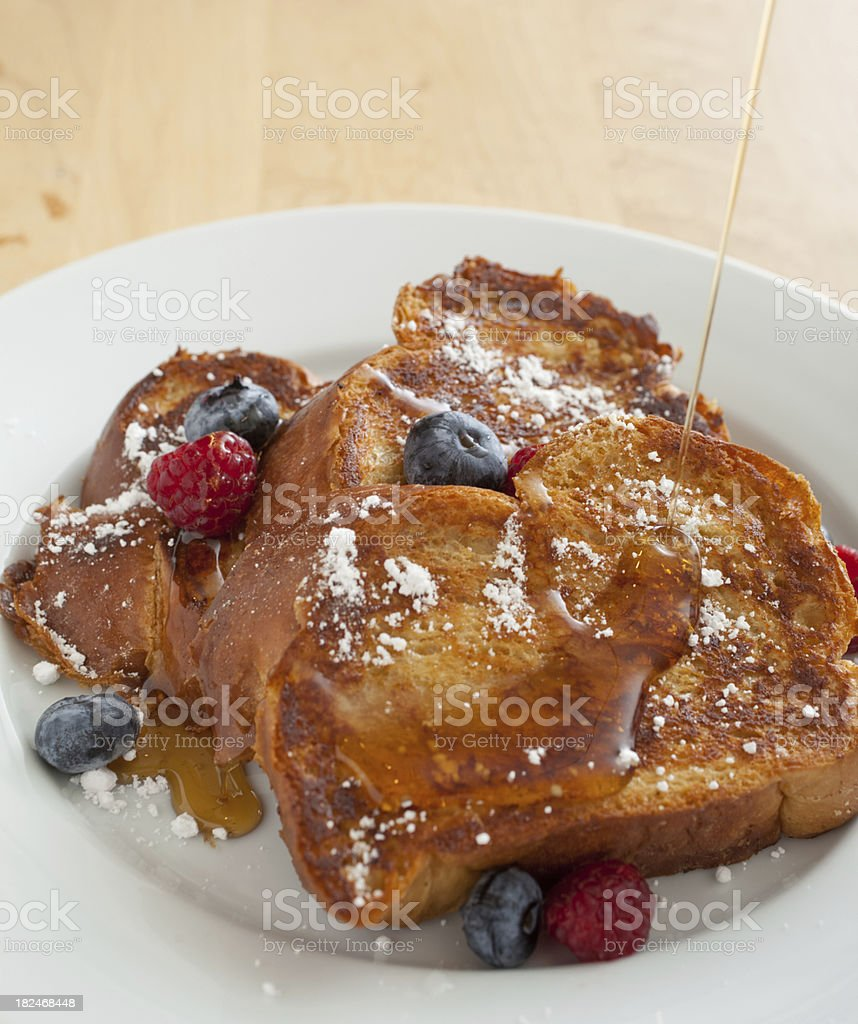Challah French Toast with Fresh Berries and Syrup Pouring royalty-free stock photo