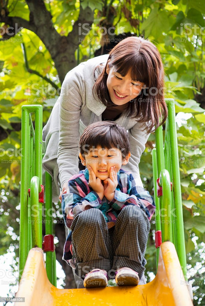 Challenge to little Asian boy, trying a slide royalty-free stock photo