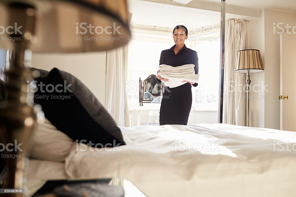 Chambermaid carrying linen in hotel bedroom, low angle view stock photo