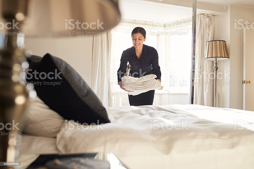 Chambermaid placing linen on hotel room bed, low angle view stock photo