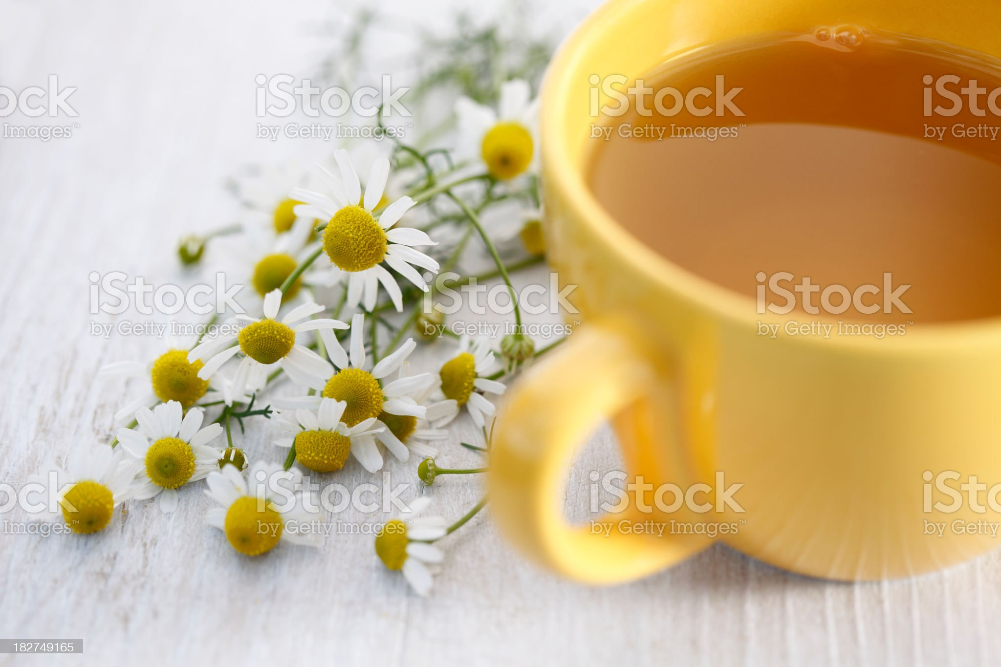 Chamomile tea in a yellow cup on white table with daisies royalty-free stock photo