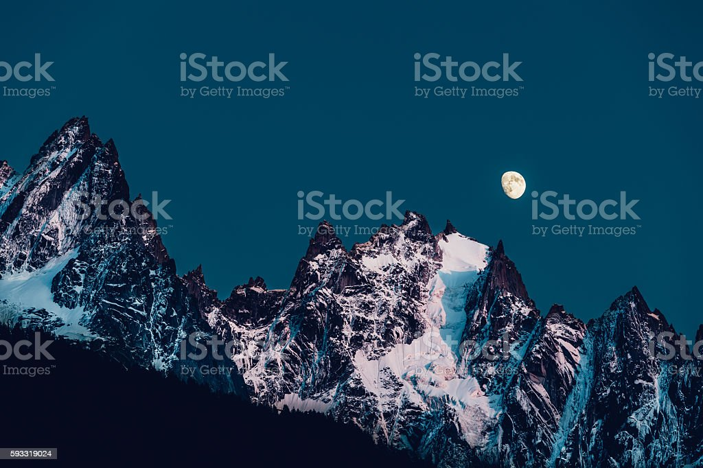 Chamonix Aiguilles with moon after dusk stock photo