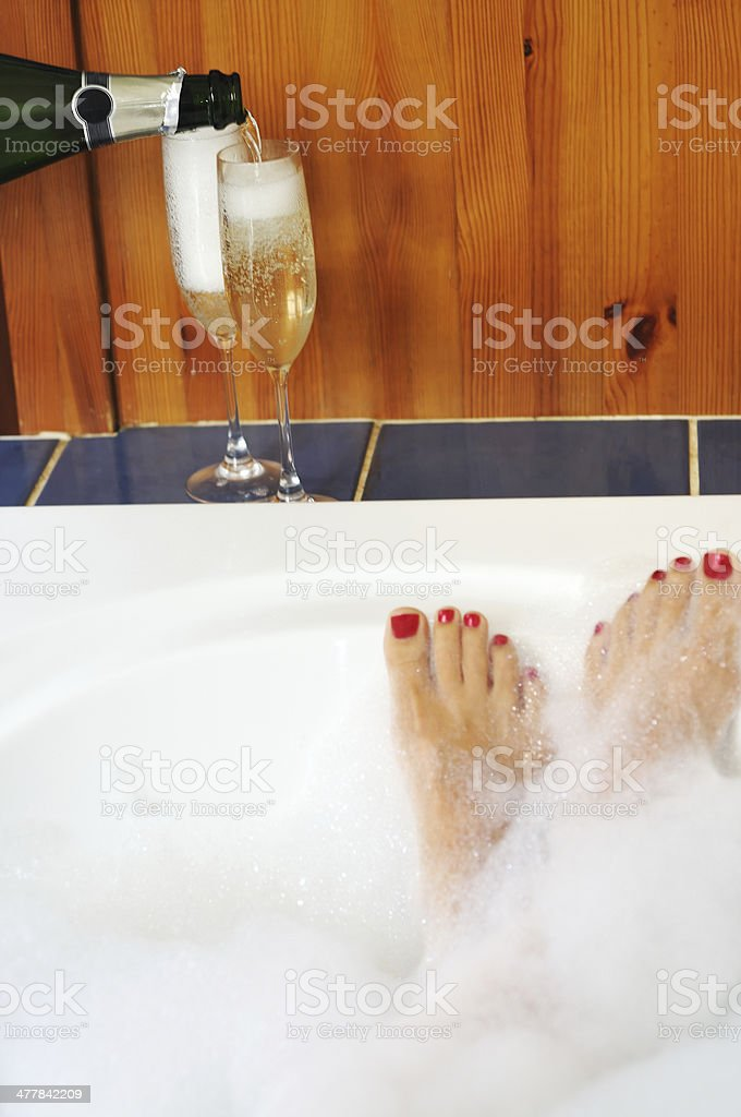 Champagne and feet up in the bath stock photo