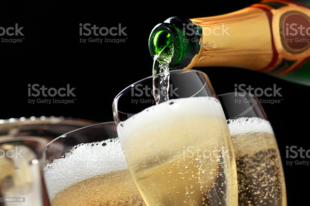 Champagne being poured into champagne glasses stock photo