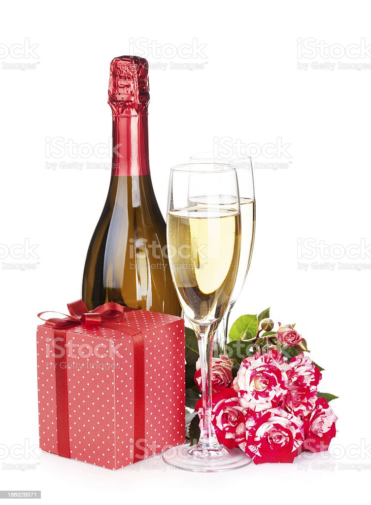 Champagne bottle, two glasses, gift box and red rose flowers royalty-free stock photo