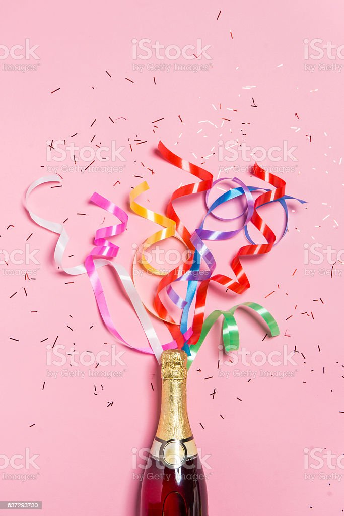 Champagne bottle with colorful party streamers on pink background. stock photo