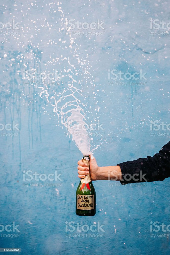 Champagne bottle with sign: Save Water drink champagne stock photo
