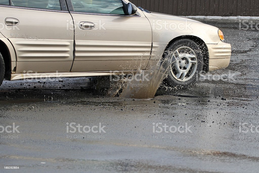 A champagne colored car hitting a pothole on a rainy day stock photo