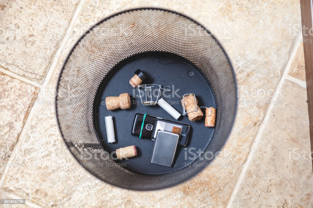 Champagne corks and mobile phone at bottom trash stock photo