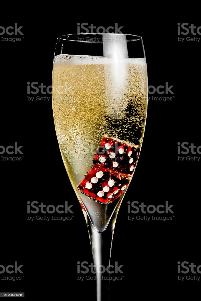 champagne flute with golden bubbles and red dice stock photo