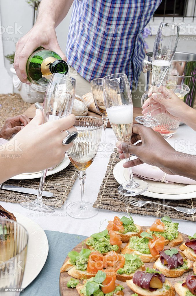 Champagne flutes and toasting among friends royalty-free stock photo