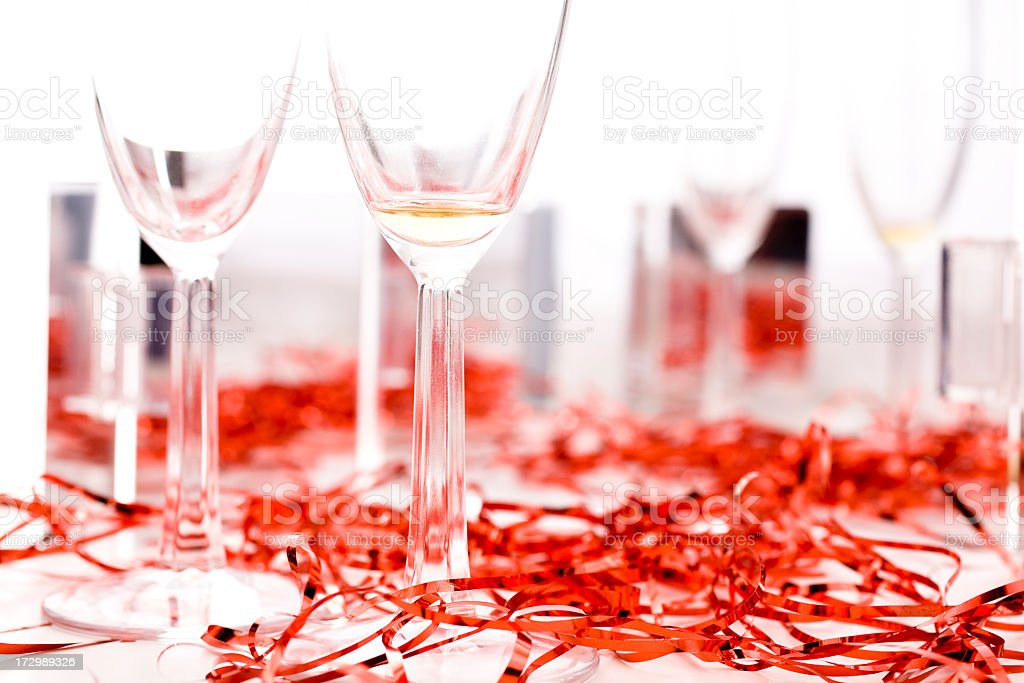 Champagne flutes with festive red streamers on table royalty-free stock photo