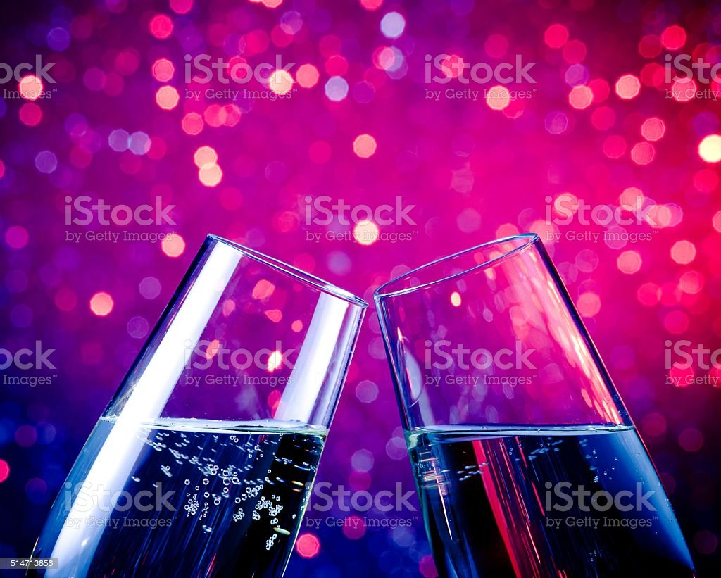 champagne flutes with gold bubbles on blue bokeh background stock photo