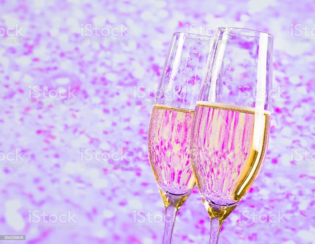 champagne flutes with gold bubbles on blur violet background stock photo