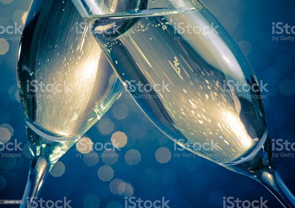 champagne flutes with golden bubbles on blue light bokeh background stock photo