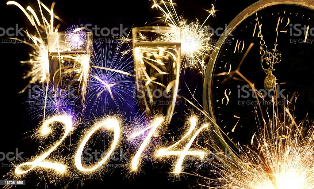 Champagne Glasses Infront Of Fireworks With Sparkling 2014 And Clock royalty-free stock photo