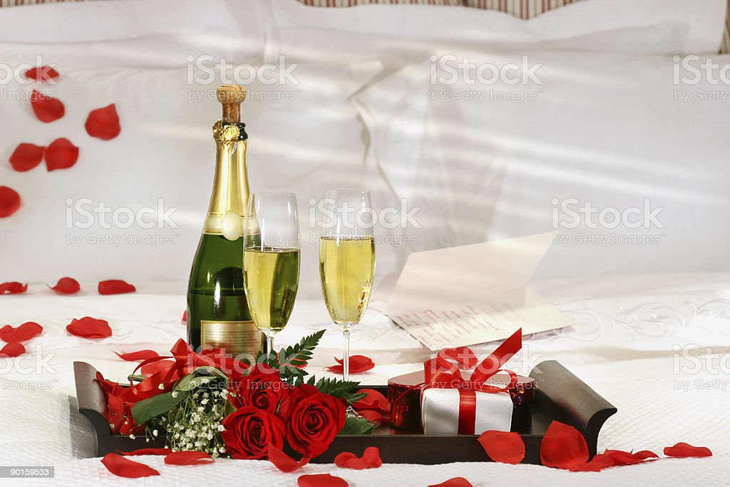Champagne, roses, and gift waiting on romantic bed stock photo