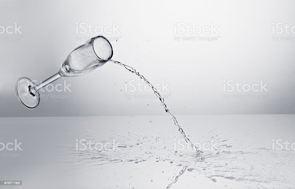 Champagne spilling from falling glass stock photo