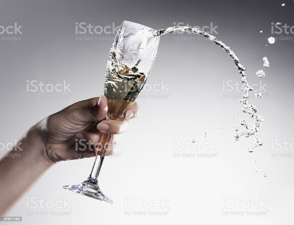 Champagne spilling from glass stock photo