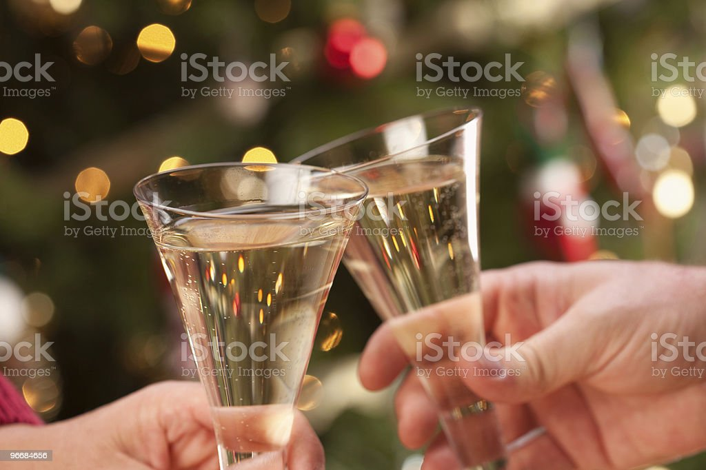 A champagne toast in front of blurred Christmas lights royalty-free stock photo