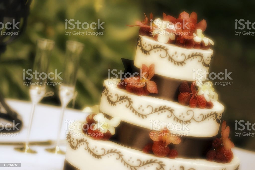 Champaign Flutes and wedding cake decorated with red flowers royalty-free stock photo