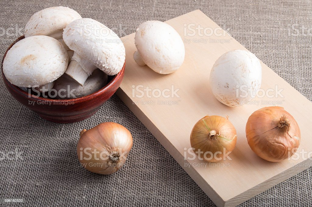 Champignon mushrooms and onions on the table stock photo