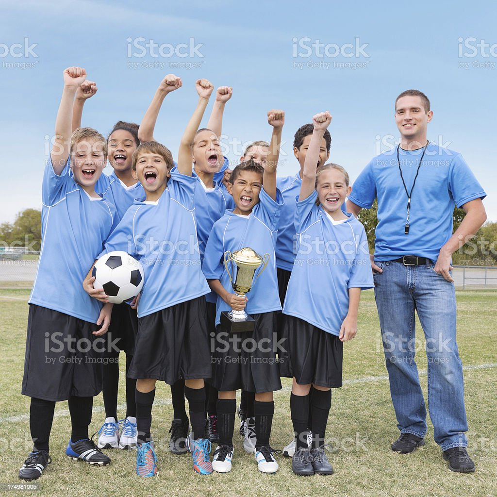 Championship kids' soccer team celebrating with coach after win stock photo