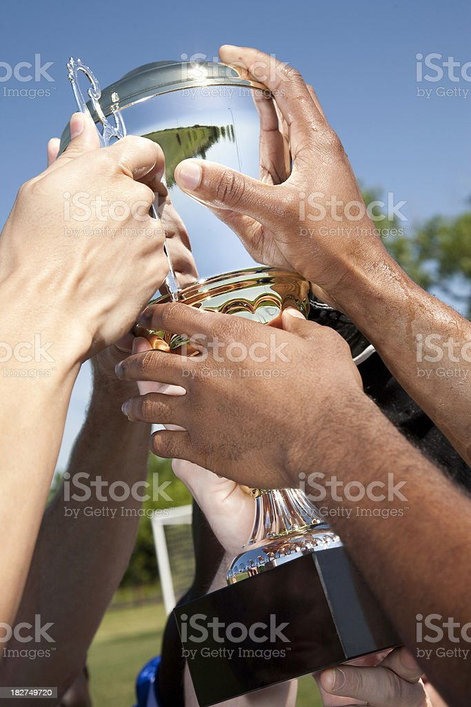 Championship Trophy Held Up By Soccer Players stock photo