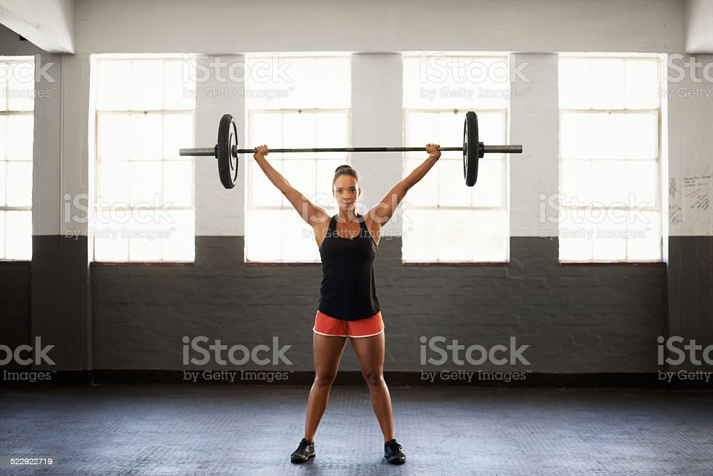 Portrait of a muscular young woman in a gym holding a barbell over...