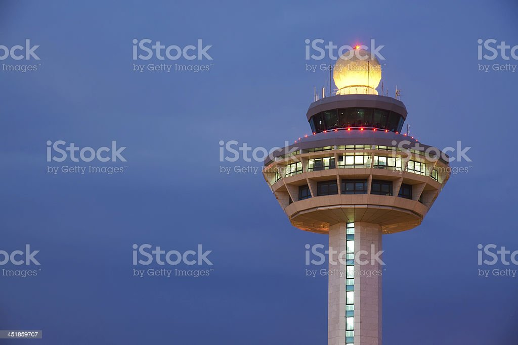 Changi Airport control tower against a dark cloudy sky stock photo