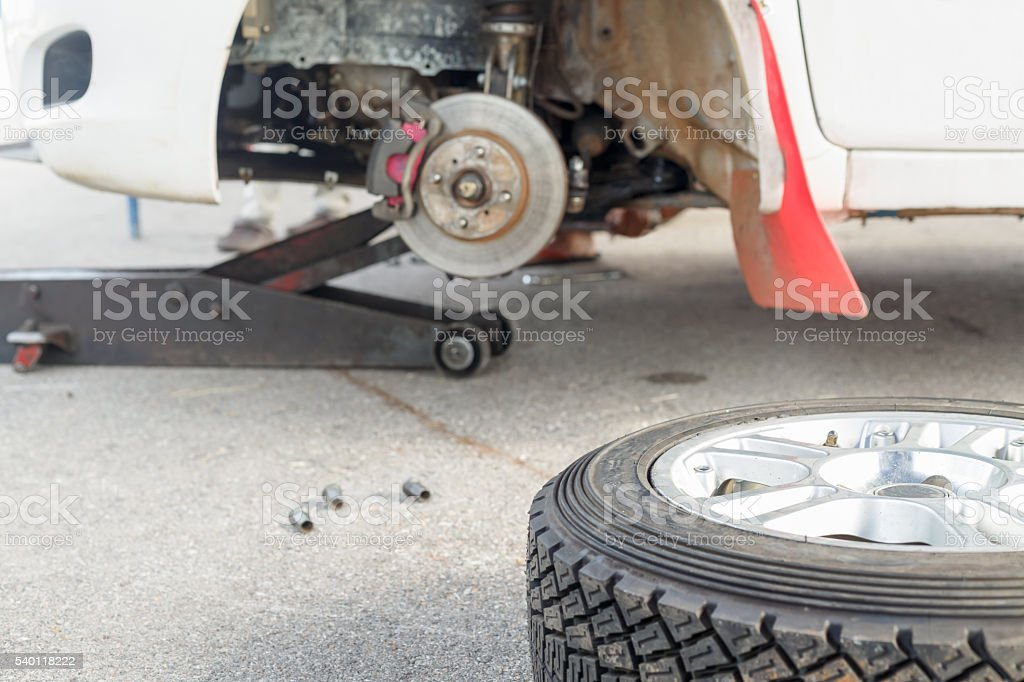 Changing a tire on a rally car in maintenance area stock photo