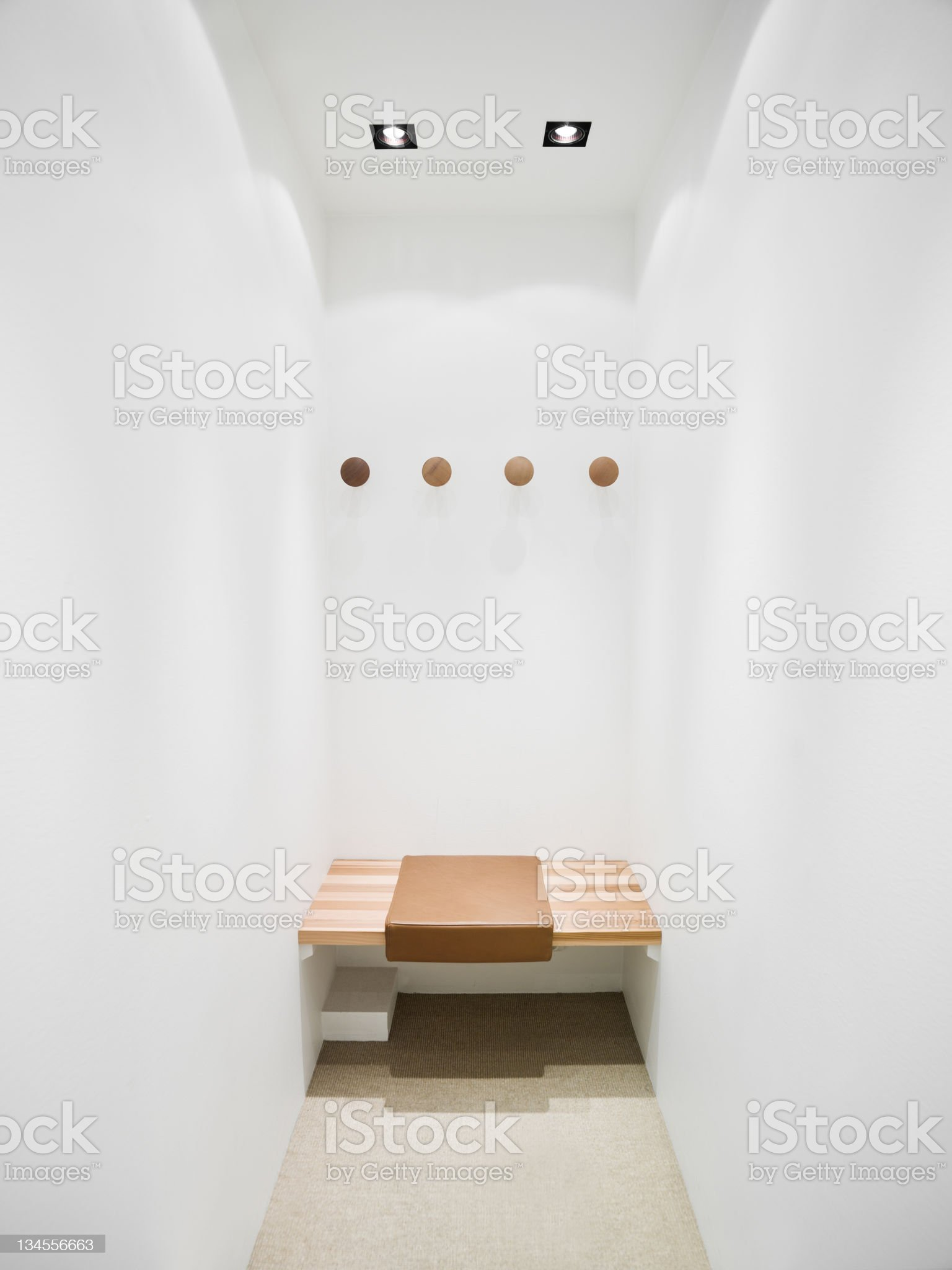 Changing room with wooden seat and white walls royalty-free stock photo