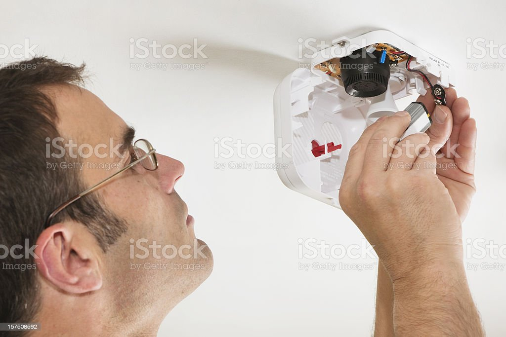 Changing the battery in a fire alarm stock photo