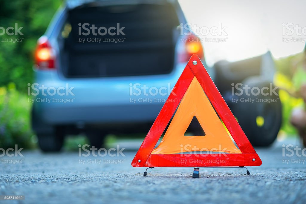 Changing the tire on broken car with red warning triangle stock photo