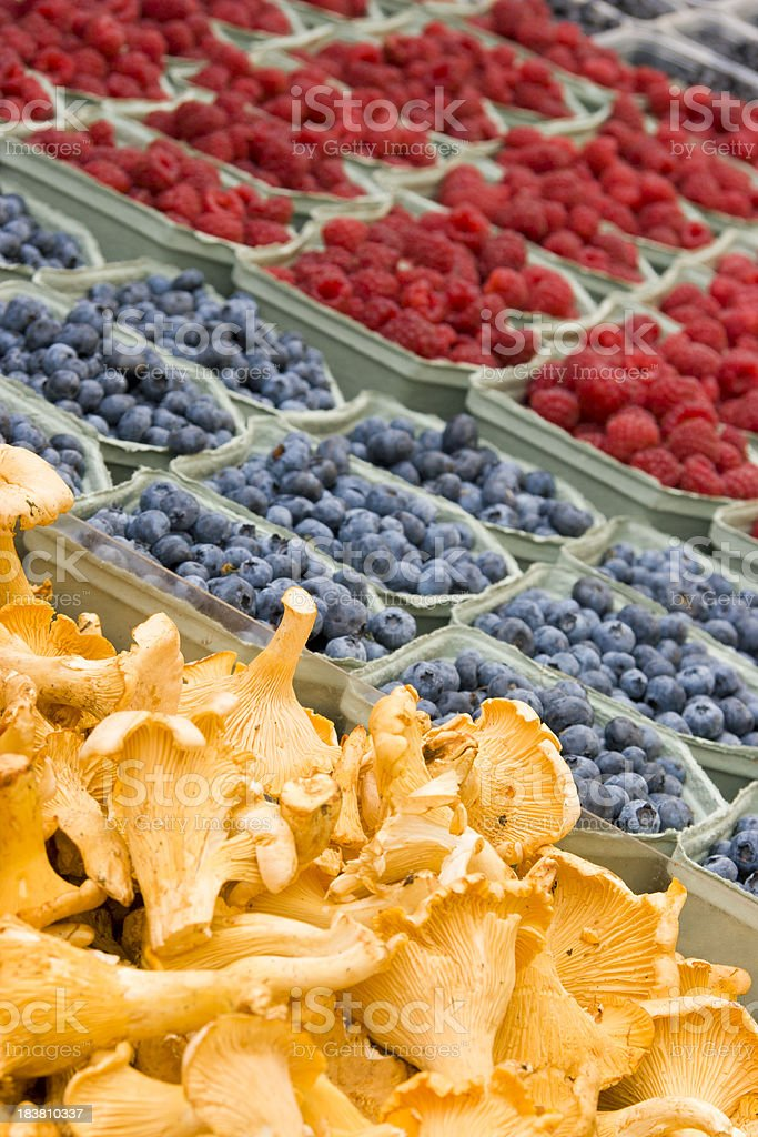 Chanterelle Mushrooms at Market, Berries in Background stock photo