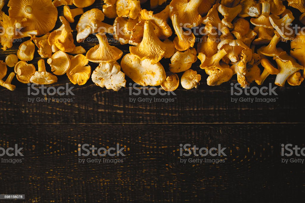 Chanterelles on the old wooden table top view stock photo