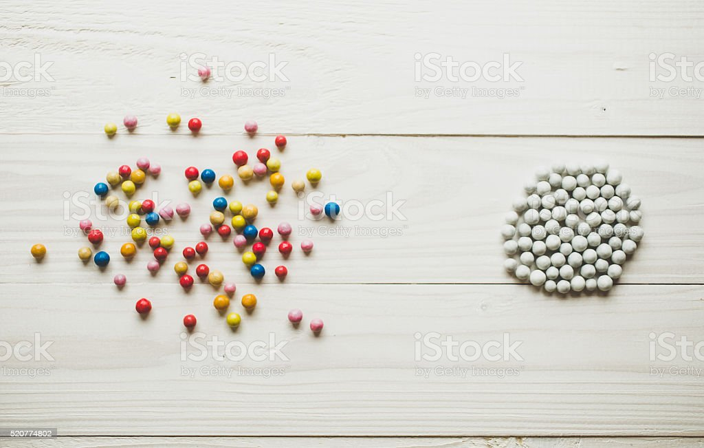 Chaotic colorful balls and organized white balls. Order and chaos stock photo
