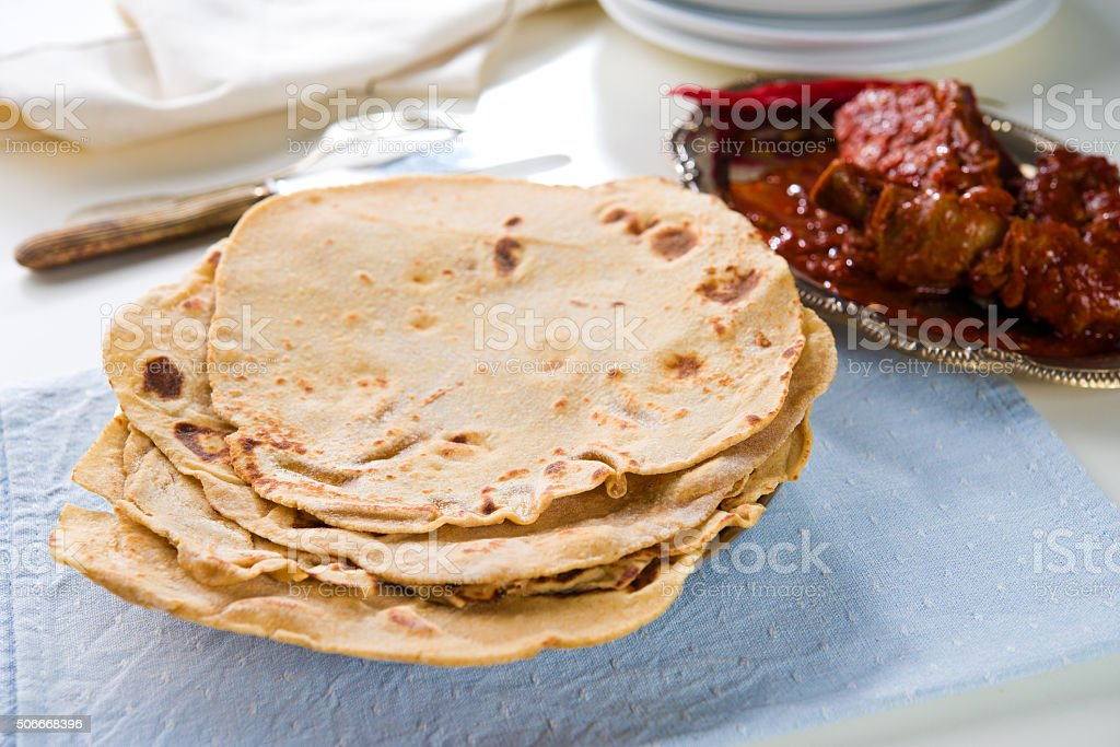 Chapatti roti and Indian food on dining table. stock photo