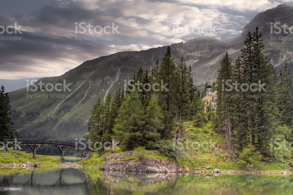 Chapel and bridge on mountain lake in summer. royalty-free stock photo